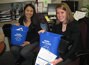 Staff holding deskside recycling bins