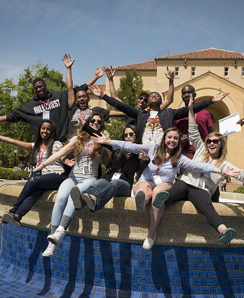 Students celebrating water conservation in an empty Stanford fountain